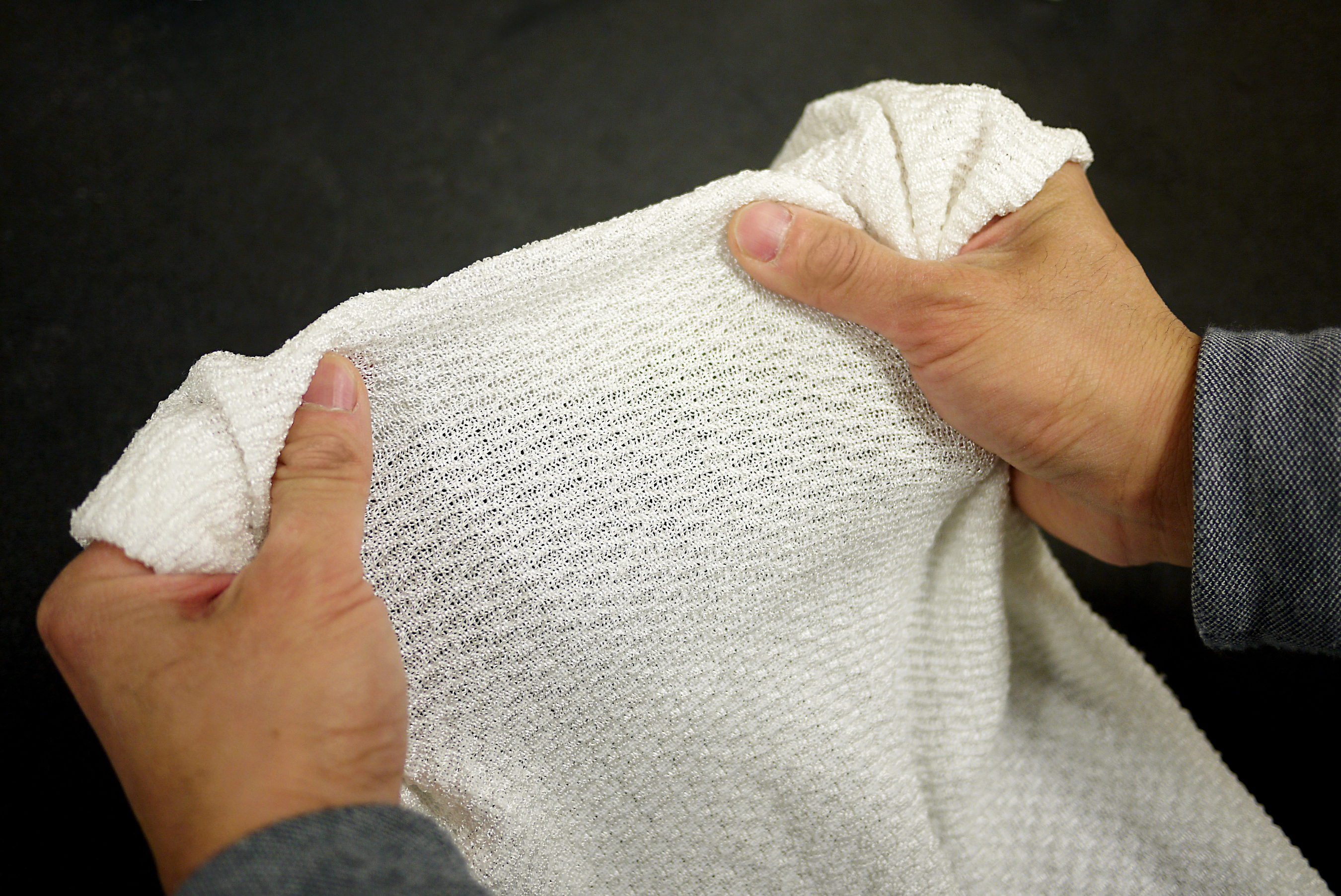 This new fabric being developed by University of Maryland scientists YuHuang Wang and Ouyang Min is the first textile to automatically change properties to trap or release heat depending on conditions. Photo: Faye Levine, University of Maryland