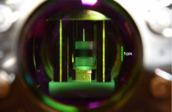 Mirrors with a green tint can be seen inside a small experimental cavity.
